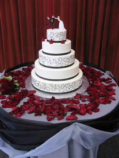 cake with rose petals surrounding it