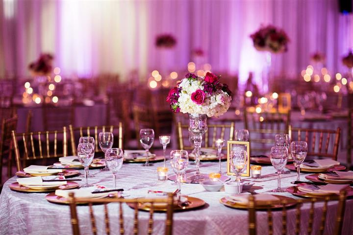 reception area with pink light accents and a focus on the gold and pink table set up