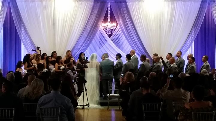 wedding in front of a purple and white curtain display