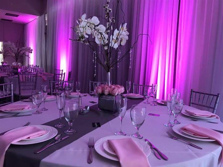 table setting with pink lighting in the background