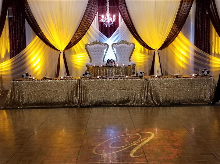 gold and red wedding ceremony with the bride and groom chairs at the head of the table