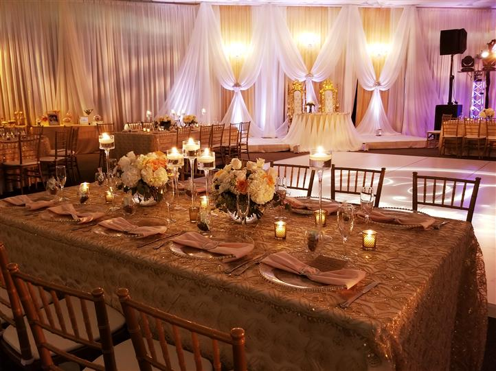 gold tablecloth table setting with candles lit