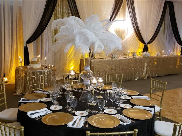table setting with black and gold accents with a vase filled with white feathers in teh middle