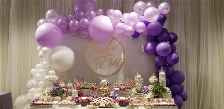 dessert table with a purple ombre balloon tower behind it