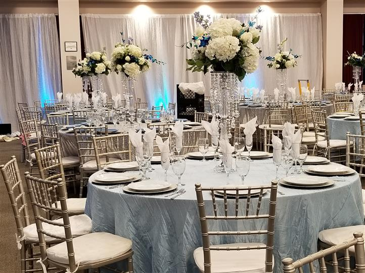 wedding set up with ice clue table clothes and large bedazzled centerpieces with white flowers