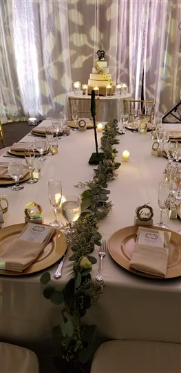 long table setting with tan plates and a table runner