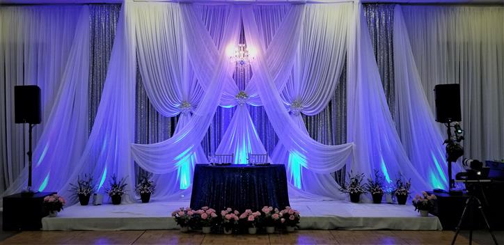 wedding backdrop with curtains and the bride/groom chairs
