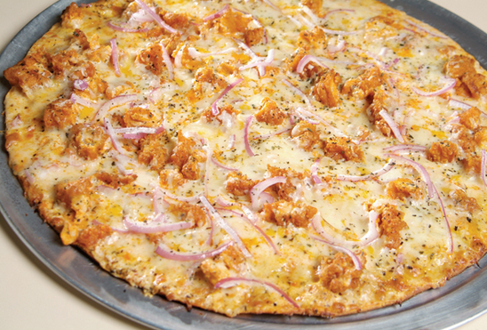pizza topped with multiple tpyes of cheese, onions and chicken