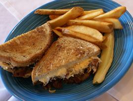sandwich with meat and melted chese, with a side of fries
