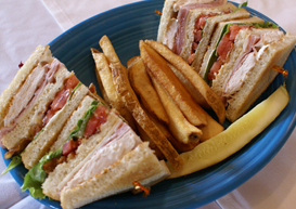sliced deli sandwich with a side of fries