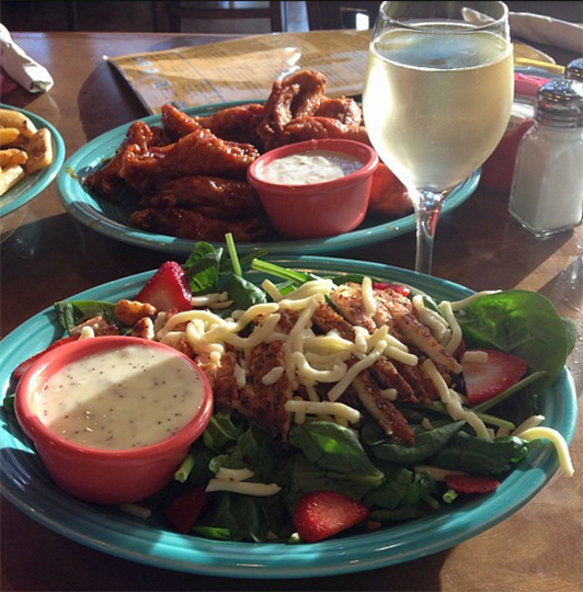 salad with chicken and strawberries, next to a plate of chicken wings