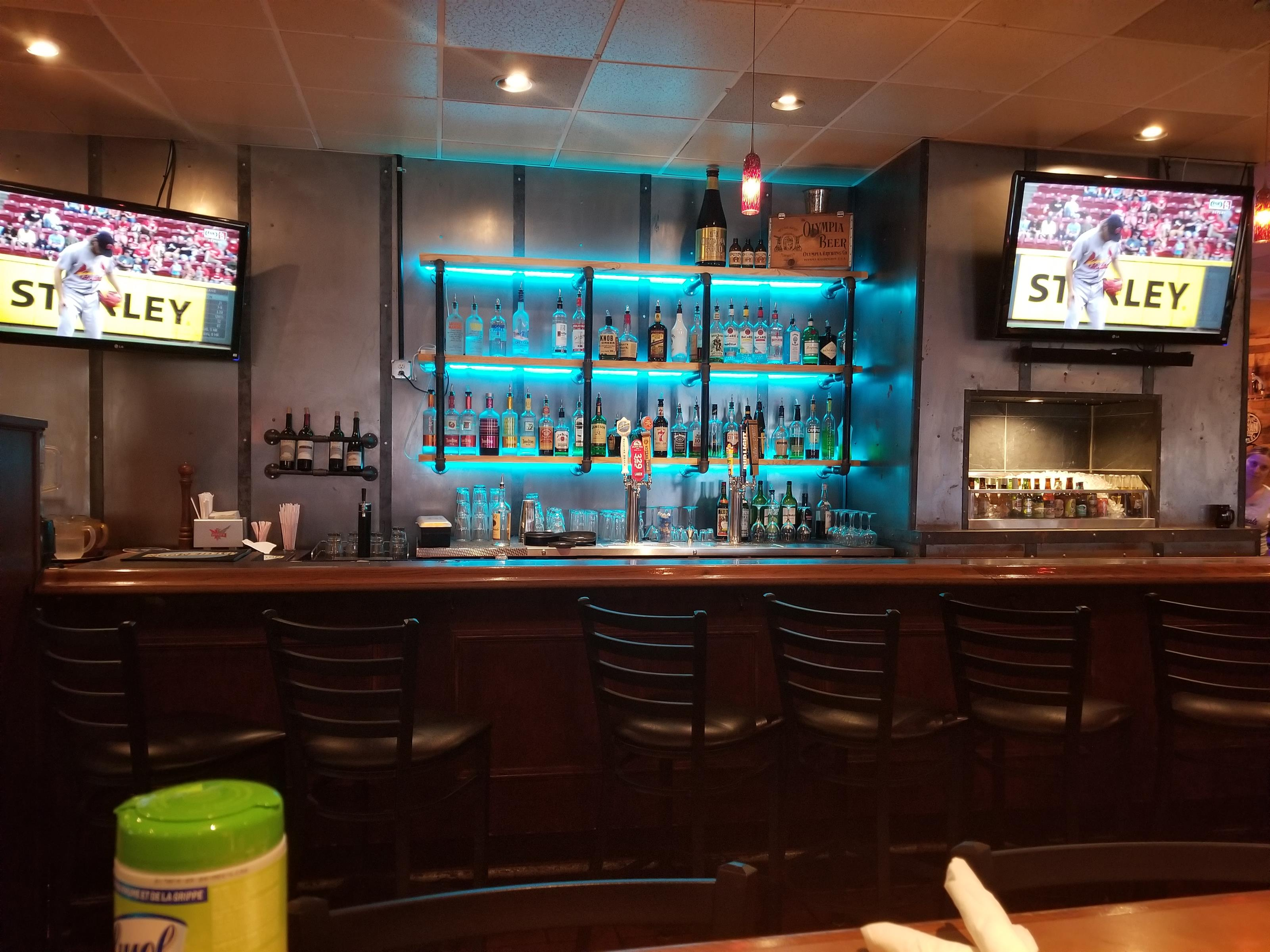 bar area with various drinks and television screens