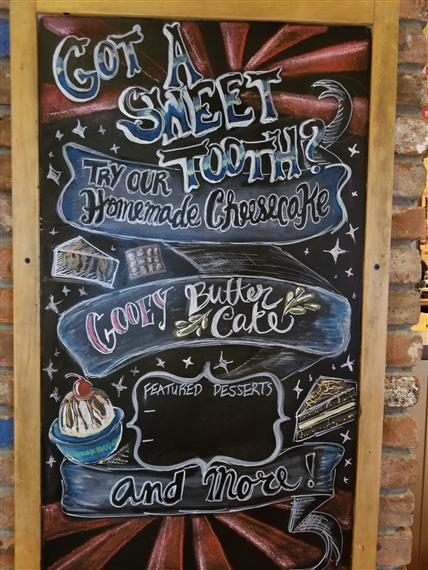 "chalkboard sign that reads, ""Got a sweet tooth? Try our homemade cheesecake, gooey butter cake, and more!"""