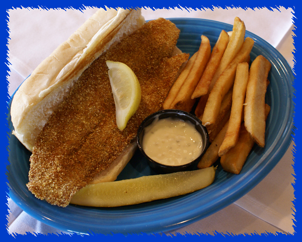 fried fish filet on a bu nwith a side of fries and tartar sauce