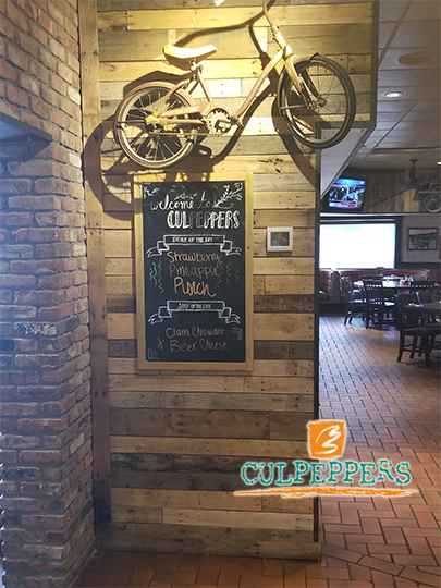 wall with bicycle mounted on it, and a chalkboard sign