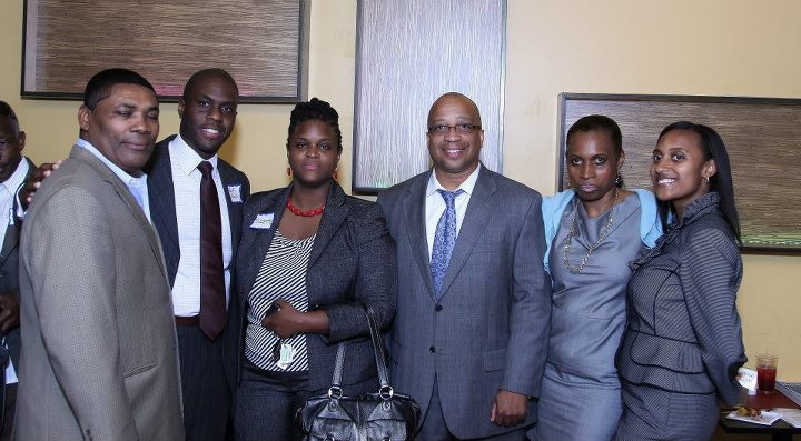 People in business attire smiling for a photo at the Caribbean Business Networking event