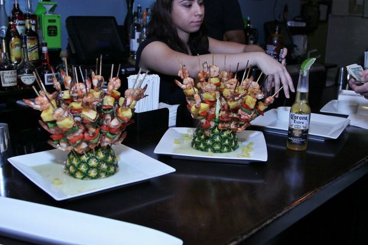 Assortment of kababs on halves of pineapples