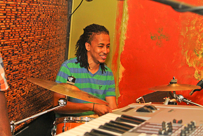 Live performer playing the drums and smiling