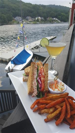 Club sandwich served with coleslaw and fries with a cocktail drink on a tall glass