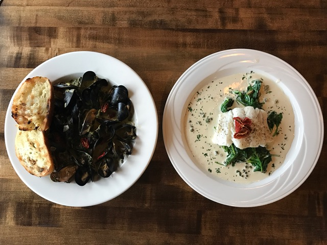A plate of steamed mussels served with  grilled bread and a plate of soup topped with greens