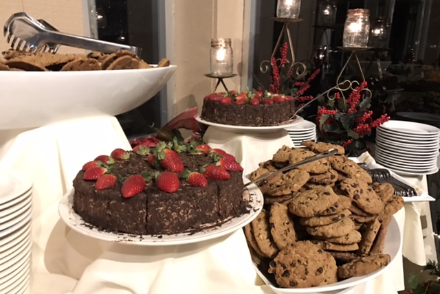 buffet table set with chocolate cakes decorated with strawberries and cookie trays