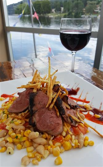 Roasted slices of meat piled over blended vegetables and topped with crispy thin fries next to a glass of red wine