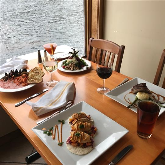 A table set wih four different servings and drinks right next to the window over the water