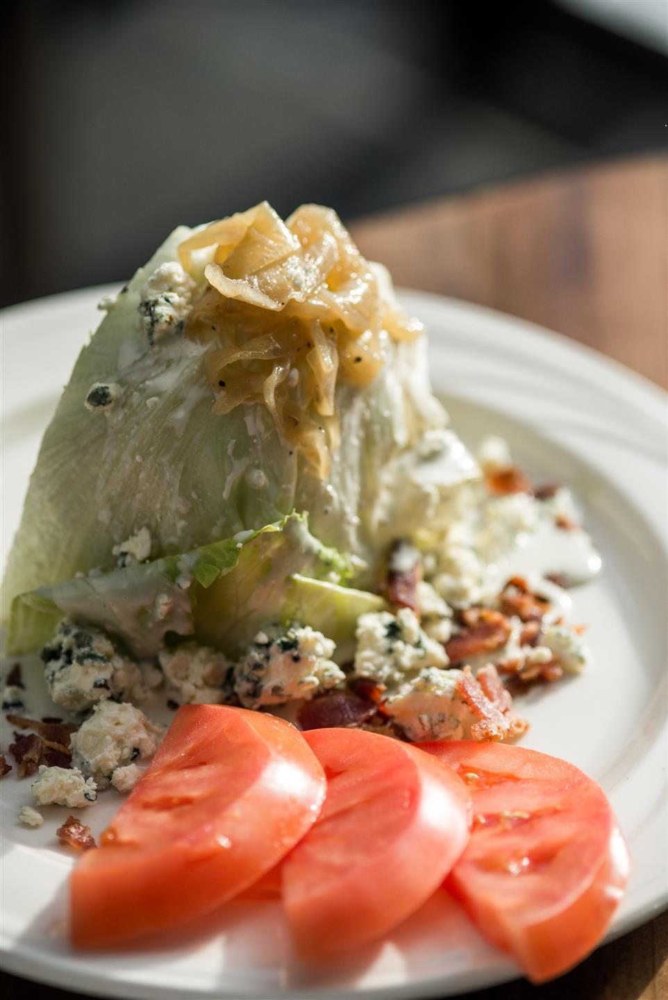 Classic Wedge Salad- Iceberg, Bailey Hazen Blue Cheese, Caramelized Onions, Bacon, Tomatoes, Blue Cheese Dressing on a white plate
