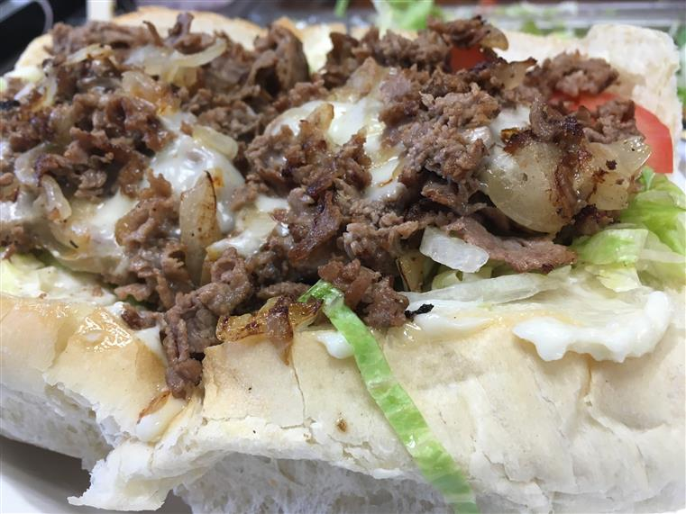 Pepper steak with lettuce, tomatoes, mayo and fried onions on bread