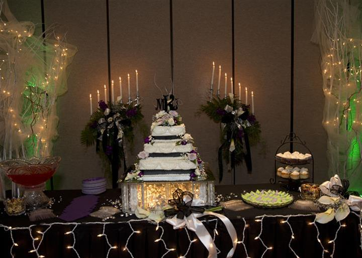 wedding cake display with candelabra, flowers, and other desserts