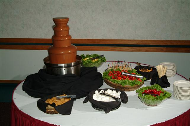 chocolate fountain display with berries, marshmallows, and cookies