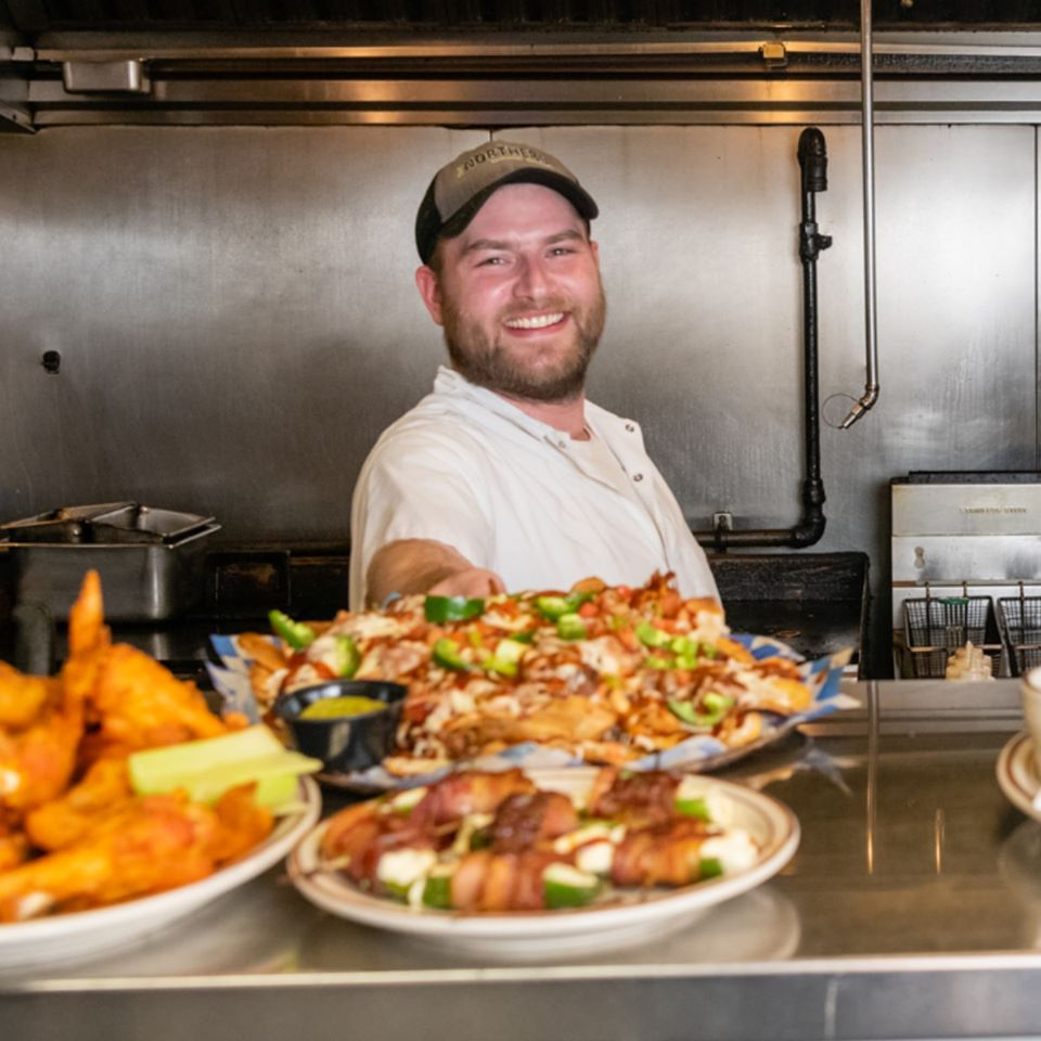 The chef smiling with multiple plates of entrees in front of him