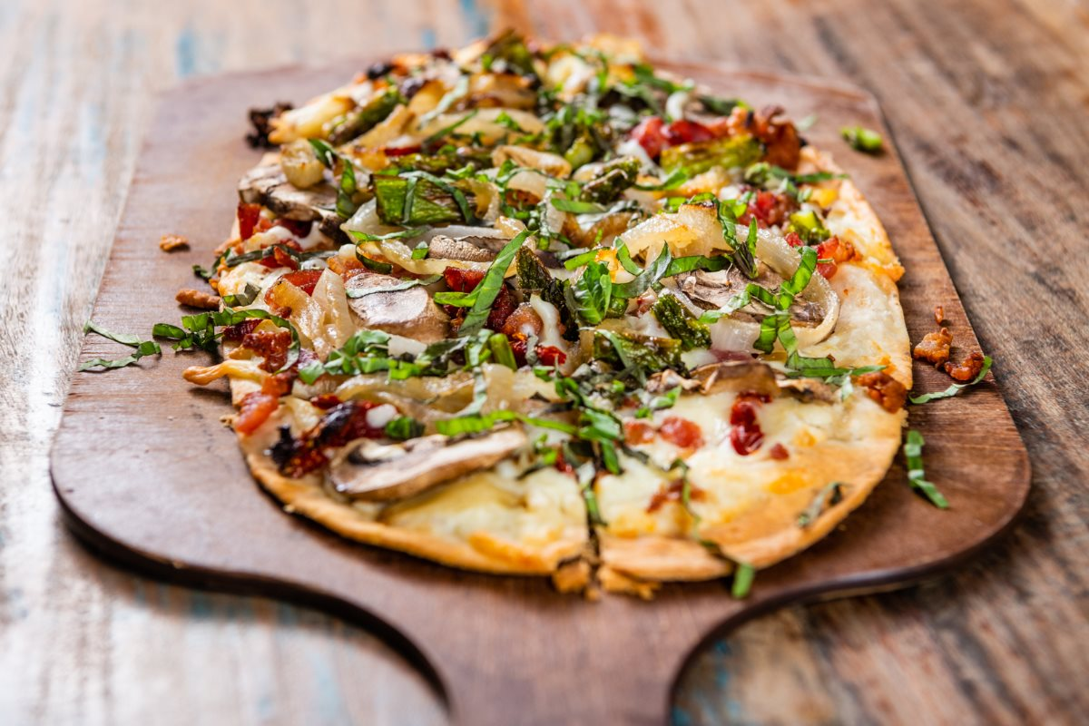 A flatbread style pizza topped with arugula and roasted vegetables