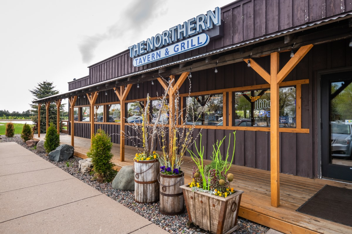 """The exterior front entrance with a sign that reads """"The Northern Lake Tavern & Grill"""""""