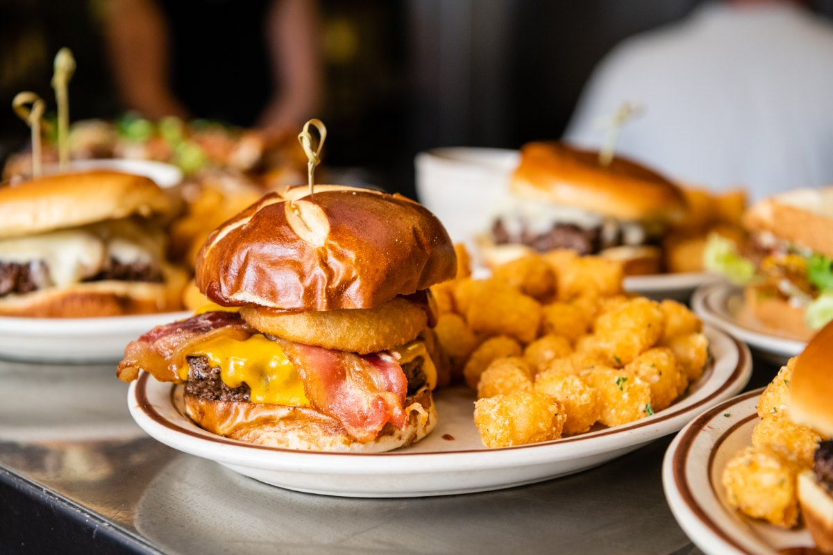 A plate with a bacon cheeseburger and tater tots on the side