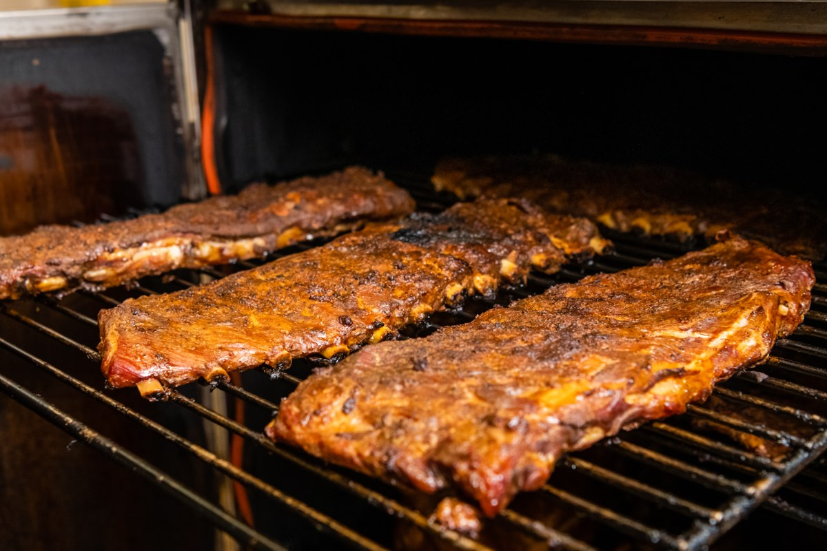 A rack of ribs cooking on the grill