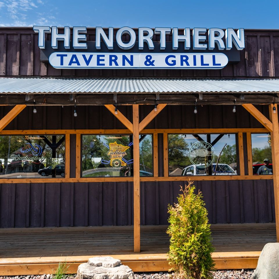 "The exterior front entrance with a sign that reads ""The Northern Lake Tavern & Grill"""