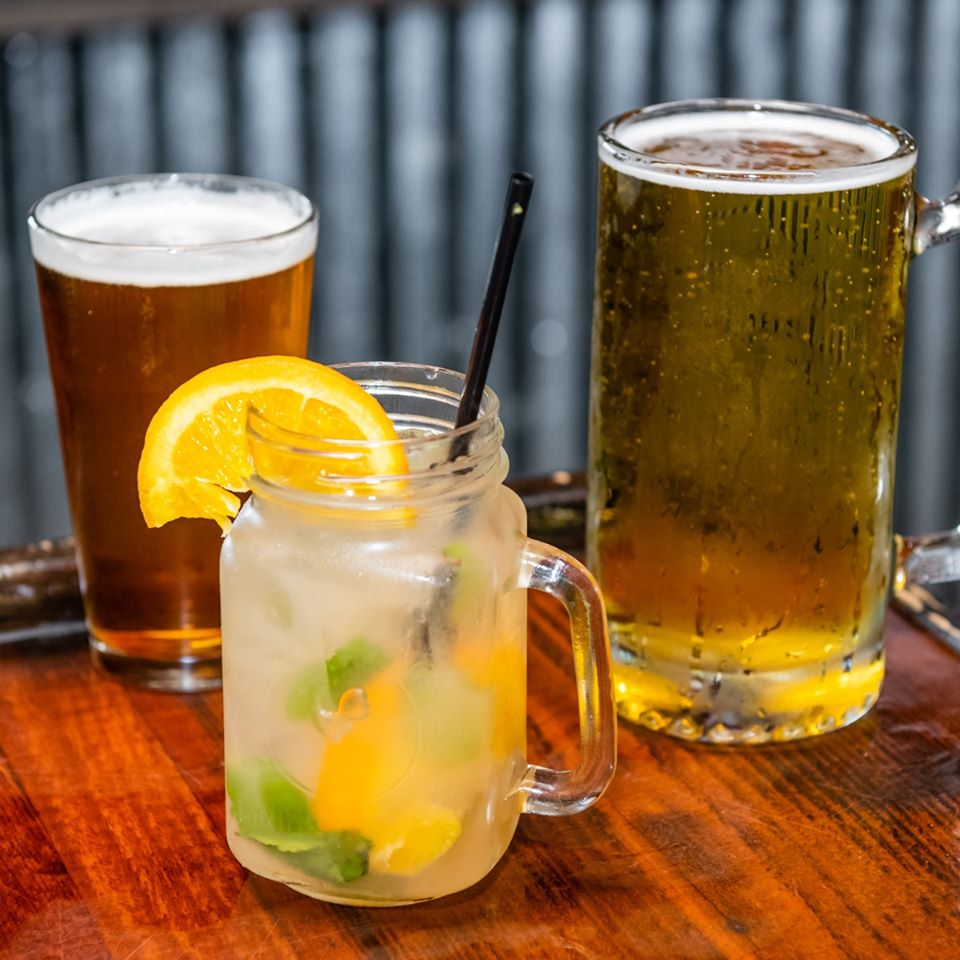 A lemon cocktail and two glasses of beer on the bar countertop