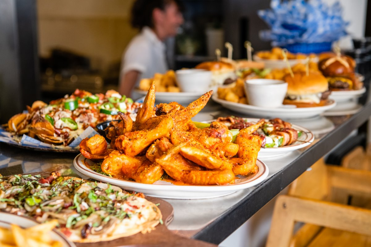 Multiple plates filled with different menu items such as fried fish, flatbread pizzas and burgers