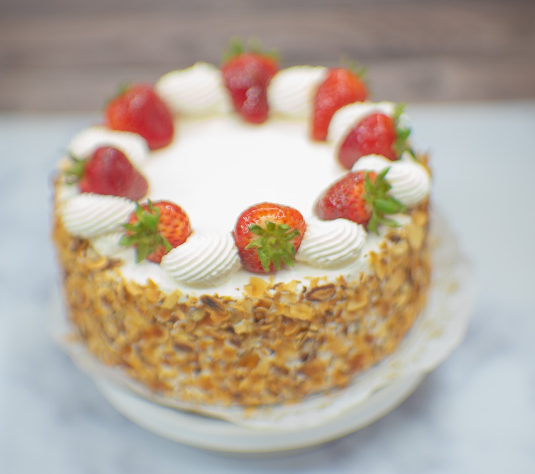 White cake with whipping cream. Fresh strawberries and toasted almonds on the side.