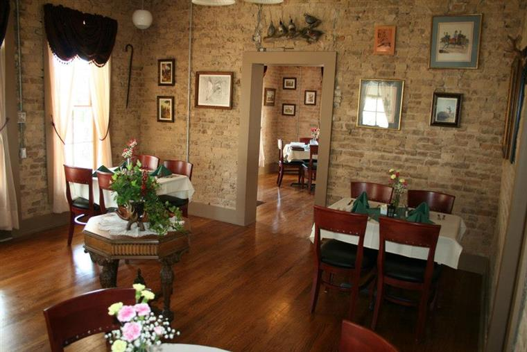Dining room with hardwood floors, white-clothed tables, chairs. Walls are faded brick. Paintings and pictures are hung on walls.