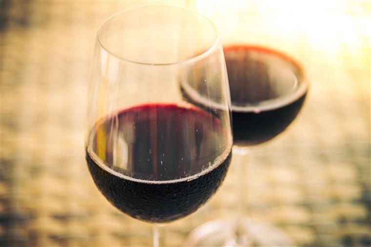Two half-filled glasses of red wine