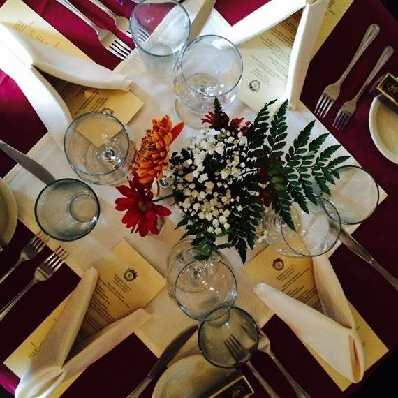 Centerpiece surrounded by empty glasses and placesettings on red-clothed table.