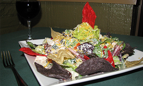 Salad with multicolored chips on white plate, red wine in background