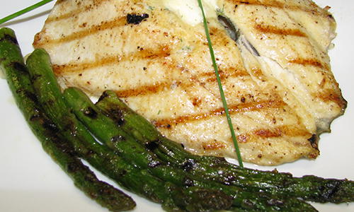 Fish and asparagus on white plate