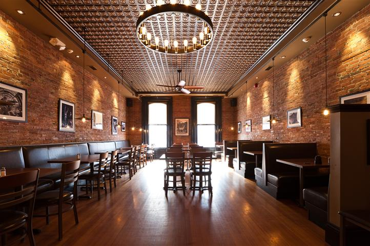 Interior. DIning room with wood floors, brick walls, chandelier on ceiling. Dark brown wood tables and chairs.