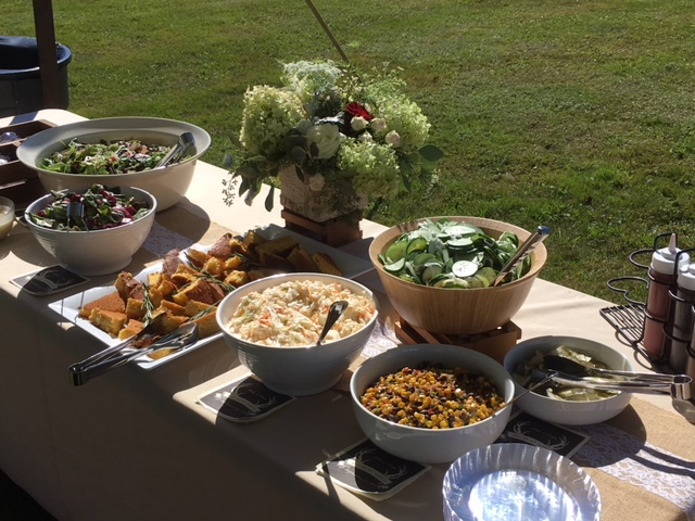 Outdoor catering table with bowls of salad, corn, cucumbers, potato salad and corn bread.