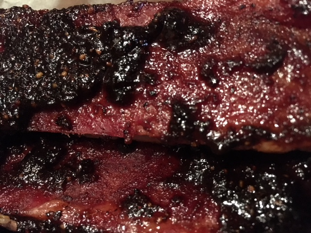 Closeup of cooked ribs with caramelized barbecue sauce