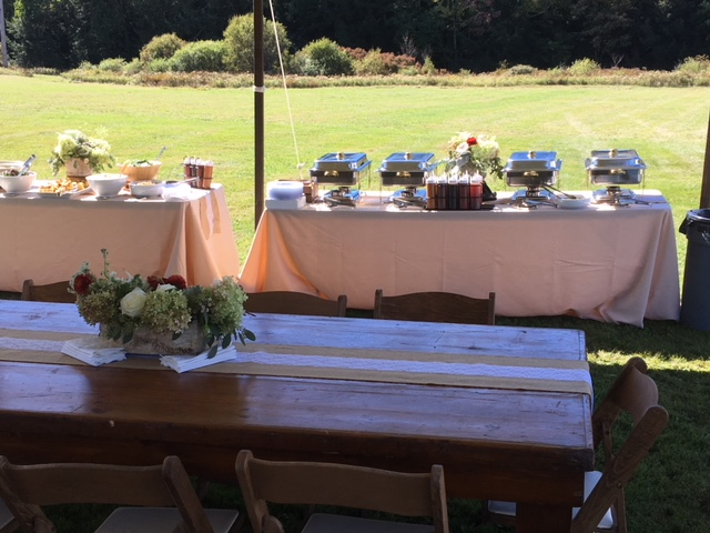 Outdoor setup of three tables, two of which have tan colored tablecloths with sternos and bowls of side dishes. Third table is wood and uncovered. Has a flower centerpiece.