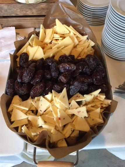 Basket of cheese and dates next to stacks of small dishes.